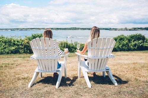 Sitting On White Adirondack Chairs